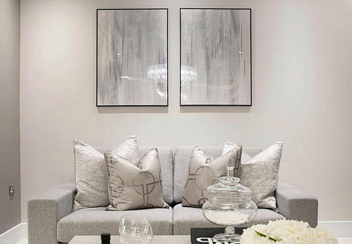 Artwork on display behind grey sofa